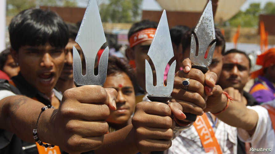 FILE - Supporters of hardline Vishwa Hindu Parishad [VHP] Hindu group hold tridents in the western Indian city of Ahmedabad, India, March 2013.
