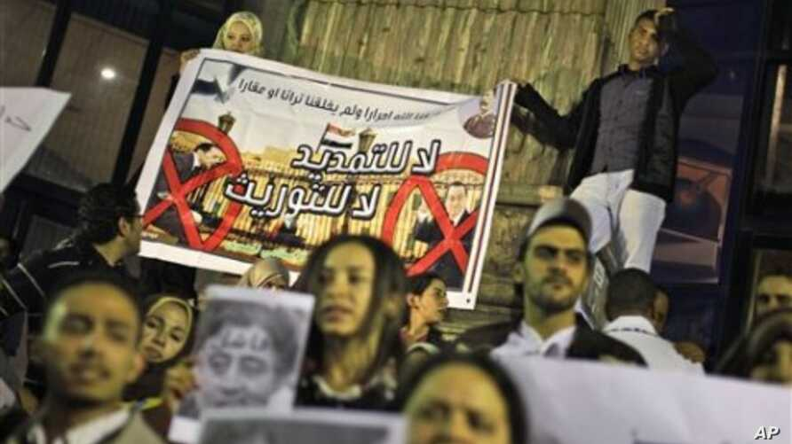 Protesters make a small demonstration of about 100 opposition activists, two holding a banner showing a photo of Egyptian President Hosni Mubarak, right, and his son Gamal Mubarak, left, in downtown Cairo, Egypt, 29 Nov 2010