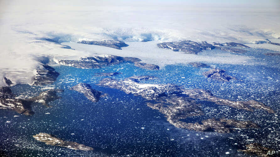 FILE - Icebergs float in a fjord after calving from glaciers on the Greenland ice sheet in southeastern Greenland. In an interview with Piers Morgan airing Jan. 28, 2018, on Britain's ITV News, the President Donald Trump said the world was cooling a