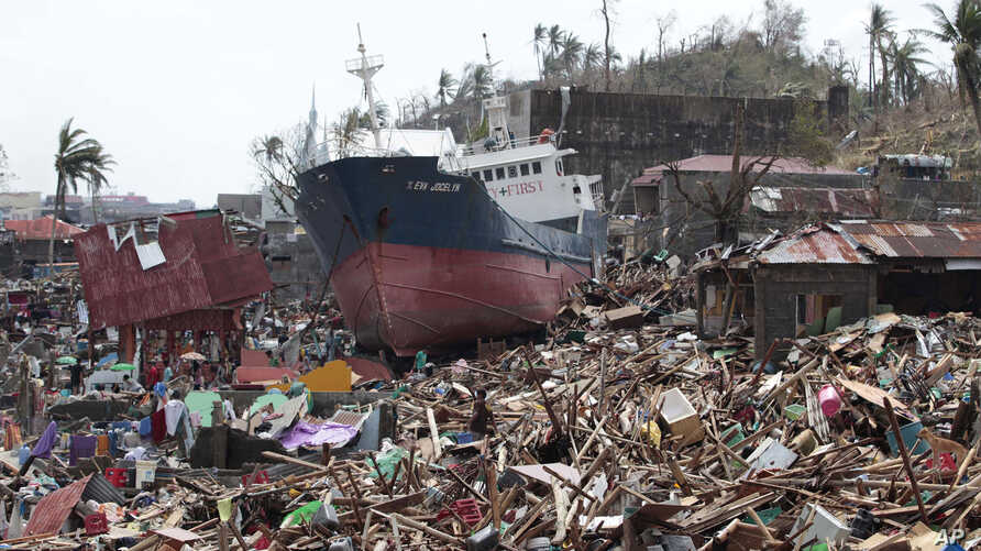 A ship lies on top of damaged homes after it was washed ashore in Tacloban city, Leyte province, central Philippines, Nov. 10, 2013.