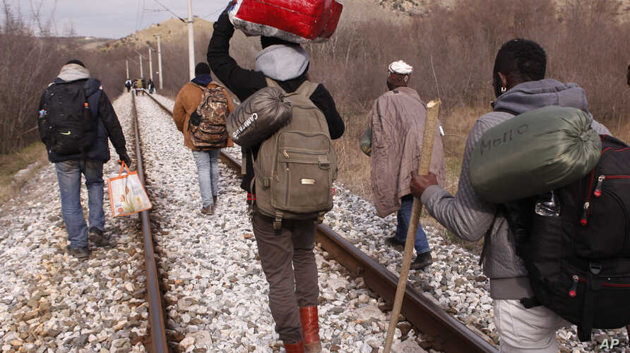 FILE - West African migrants walk on train tracks on their way to the Greek-Macedonian border near the town of Evzonoi, Greece, Feb. 28, 2015.
