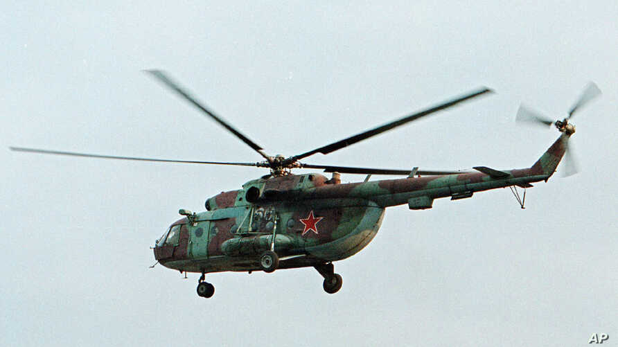 FILE - In this in this Sept. 18, 2002 file photo a Mi-8 helicopter flies over the Chechen regional capital Grozny, Russia. A helicopter similar to the one pictured has been shot down in Syria and Russian President Vladimir Putin's spokesman says all