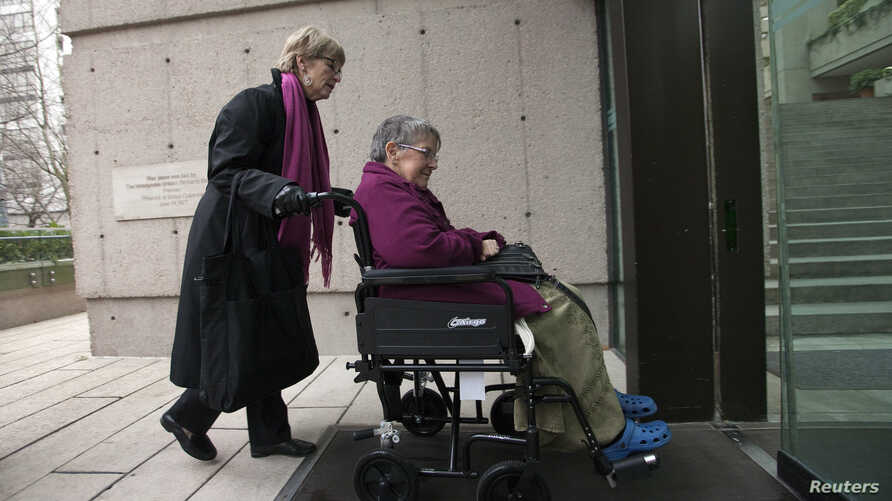 FILE - Gloria Taylor (R) enters the B.C Supreme Court with the help of Lee Carter, a fellow plaintiff in the case challenging the law regarding assisted-suicide in Vancouver, British Columbia  on Dec. 1, 2011.
