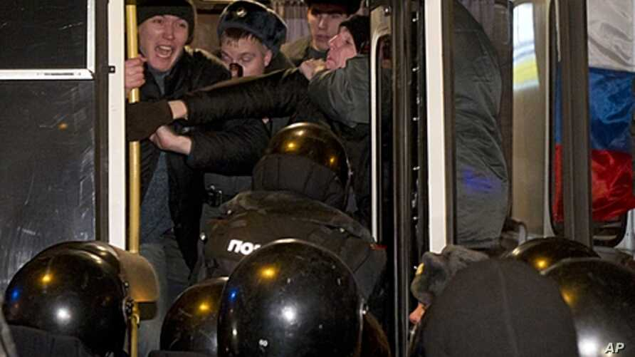 Russian police officers push detained opposition activists inside a police bus during an unsanctioned rally in downtown Moscow, December 31, 2011.