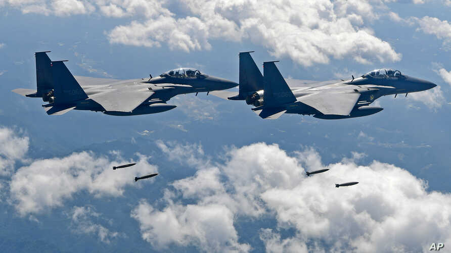 FILE - In this photo provided by South Korea Defense Ministry, South Korean air force F-15K fighter jets drop bombs as they fly over the Korean Peninsula during a joint drills with the U.S., Sept. 18, 2017. On Thursday, the air force said one of its ...