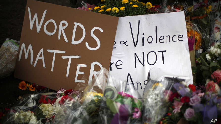 Flowers surround signs on Oct. 31, 2018, part of a makeshift memorial outside the Tree of Life synagogue to the 11 people killed during worship services Oct. 27, 2018, in Pittsburgh.