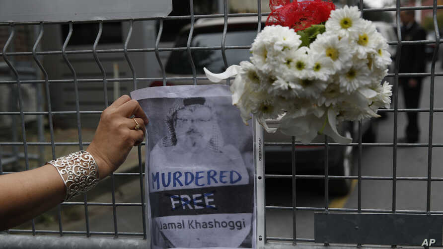Sahar Zeki, an activist and a friend of slain Saudi writer Jamal Khashoggi, attaches a picture of him and a bouquet of flowers on the barriers blocking the road leading to Saudi Arabia's consulate in Istanbul, Oct. 23, 2018.