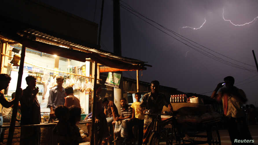 People gather at a local shop during a thunderstorm in the outskirts of Dhaka, Banglaesh, March 29, 2010.