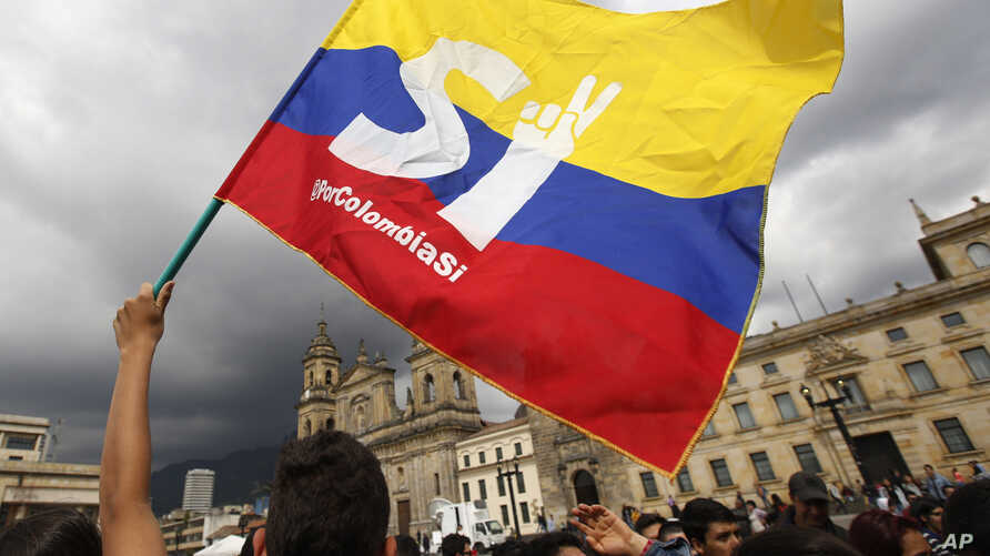 FILE -- A supporter of the peace deal between the Colombian government and rebels of the Revolutionary Armed Forces of Colombia waves a flag during a rally in front of Congress, in Bogota, Colombia, Monday, Oct. 3, 2016. After Colombians rejected the