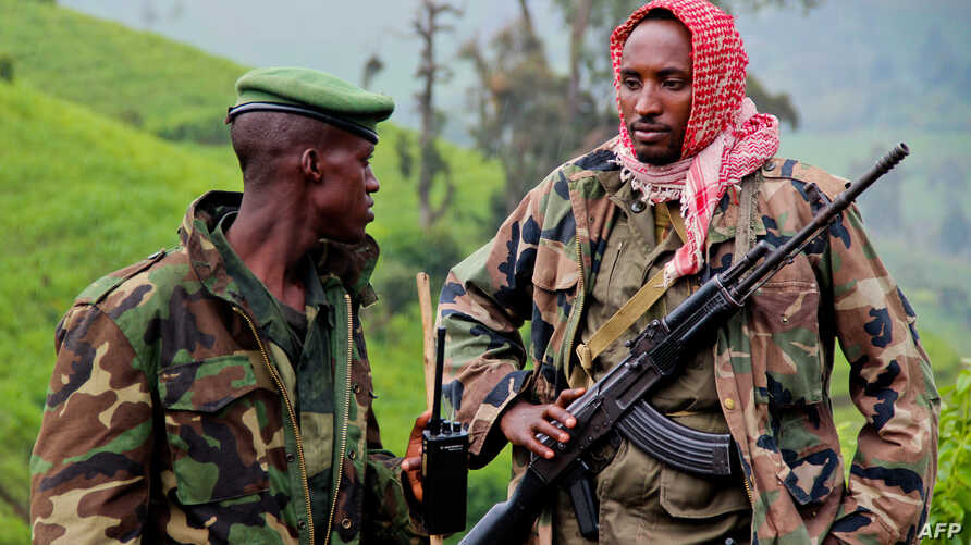A picture taken on June 3, 2012 shows rebels of the mutinous armed force known as M23 patrolling on the hill of Kavumu in North Kivu, Democratic Republic of the Congo (DRC).