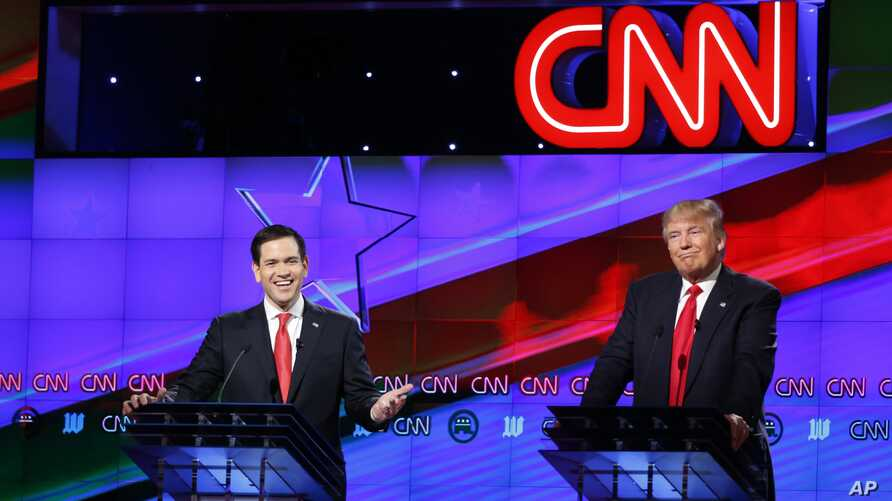 Republican presidential candidate, Sen. Marco Rubio, R-Fla., smiles, as Republican presidential candidate, businessman Donald Trump, grimaces, during the Republican presidential debate sponsored by CNN, Salem Media Group and the Washington Times at t