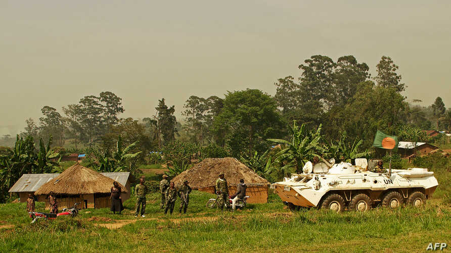 A Bangladeshi patrol from the United Nations Organization Stabilization Mission in the Democratic Republic of the Congo (MONUSCO) passes by Congolese soldiers in Gety, near Kaswara, Ituri province, on Jan. 26, 2016.