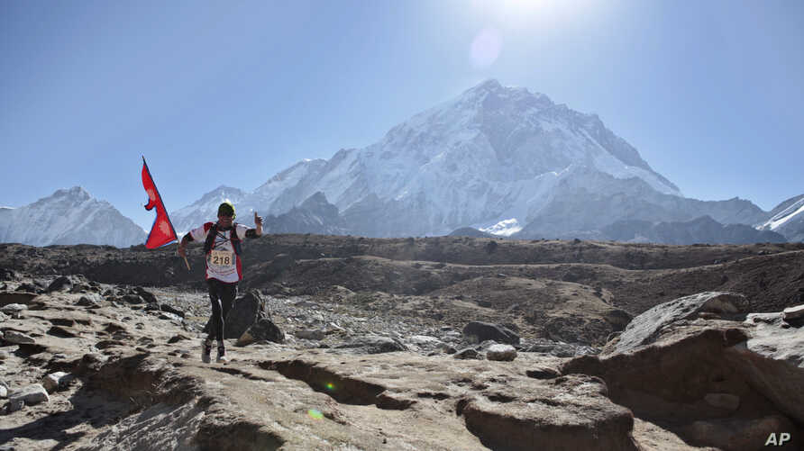 A Nepalese runs with his national flag during a marathon to mark the first conquest of Mount Everest, at Lobuche, near Everest base camp, Nepal, Monday, May 29, 2017.