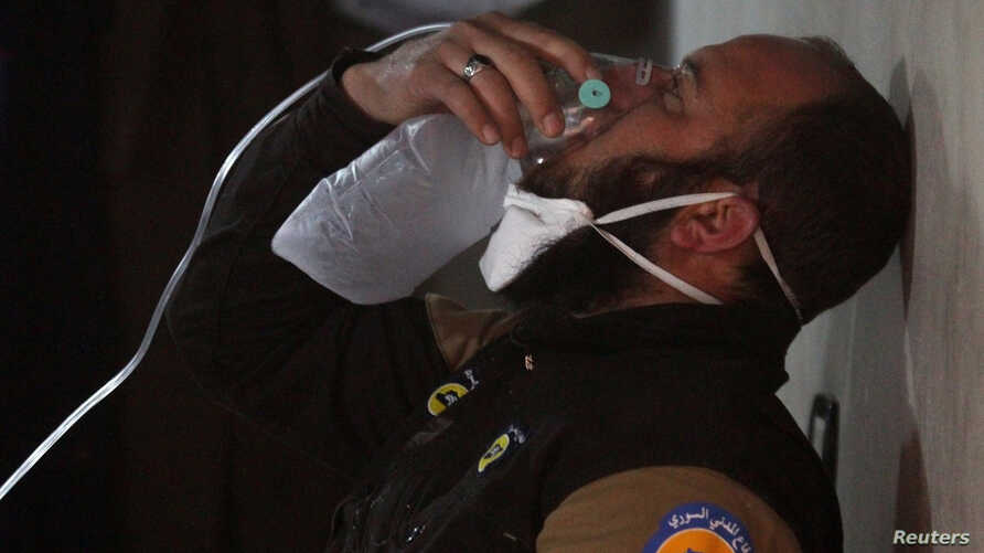 A civil defense member breathes through an oxygen mask, after what rescue workers described as a suspected gas attack in the town of Khan Sheikhoun in rebel-held Idlib, Syria April 4, 2017.