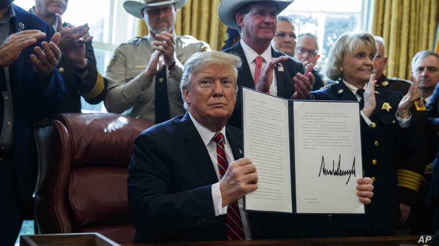 President Donald Trump signs the first veto of his presidency in the Oval Office of the White House, March 15, 2019, in Washington. Trump issued the first veto, overruling Congress to protect his emergency declaration for border wall funding.