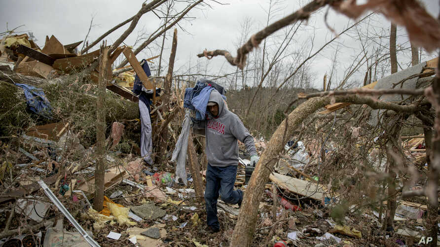 Danny Allen helps recover belongings while sifting through the debris of a friend's home destroyed by a tornado in Beauregard, Alabama,  March 4, 2019.