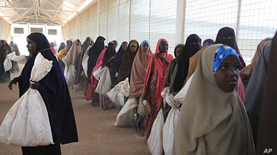 Somali refugees wait in line to receive food rations at a World Food Program distribution point in Ifo Camp, outside Dadaab, Kenya, July 15, 2011