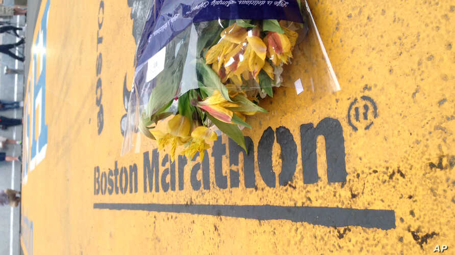 Flowers rest at the finish line of the Boston Marathon after the verdict in the penalty phase of the trial of Marathon bomber Dzhokhar Tsarnaev, May 15, 2015, in Boston. Tsarnaev was sentenced to death by lethal injection in the 2013 attack. Robert L