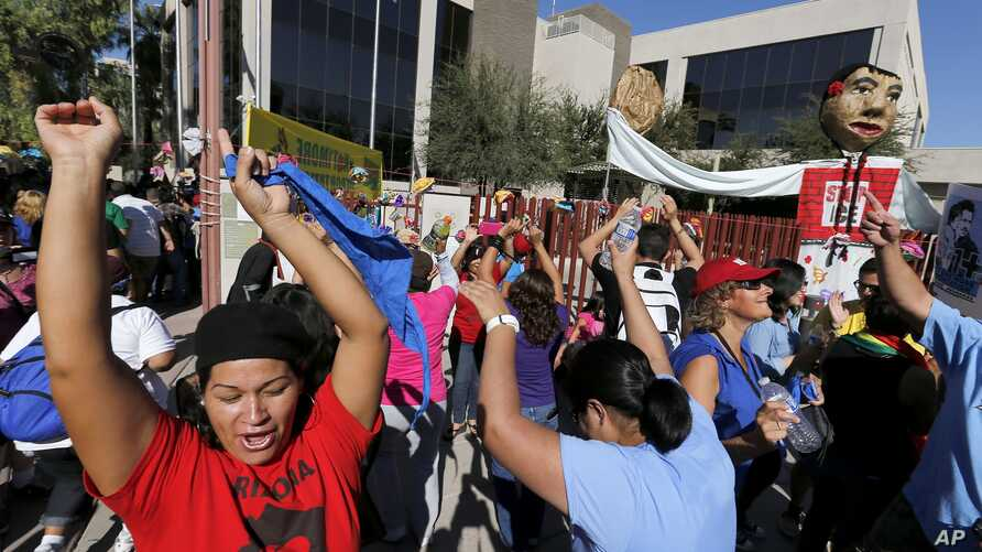 Protesters dance in front of the U.S. Immigrations and Customs Enforcement office with a goal of stopping future deportations on Monday Oct. 14, 2013, in Phoenix.