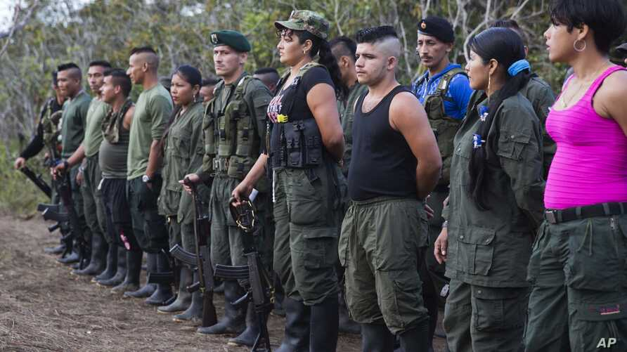 FILE - Rebels of the Revolutionary Armed FOrces of Colombia, FARC, stand on formation at their camp next to the site where is the group is holding it's 10th conference in the Yari Plains, Colombia, Sept. 17, 2016.