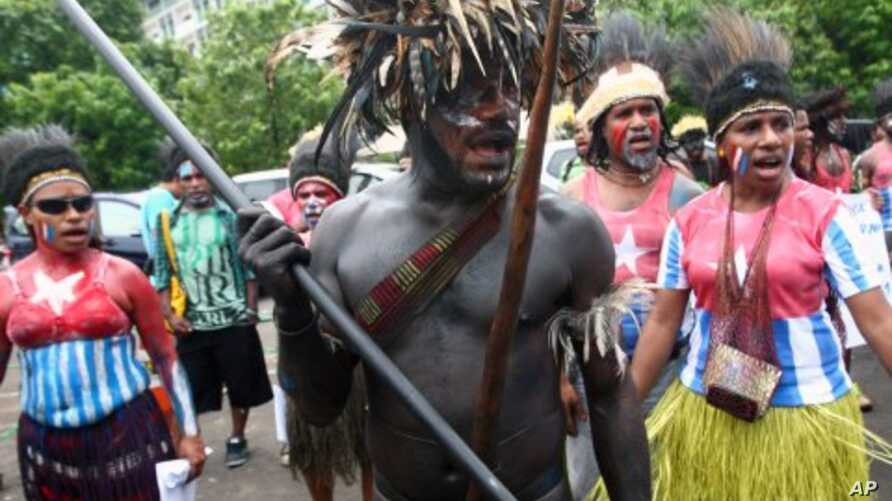 Papuan activists in traditional costumes and shirts painted with the colors of 'Morning Star' separatist flag take part in a rally marking the 50th anniversary of failed efforts by Papuan tribal chiefs to declare independence from Dutch colonial rule