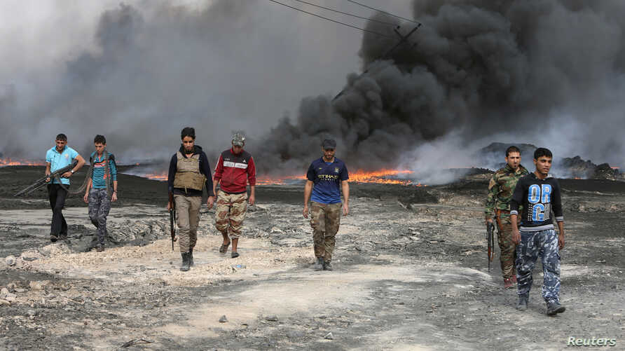 Tribal fighters walk as fire and smoke rises from oil wells, set ablaze by Islamic State militants before IS militants fled the oil-producing region of Qayyara, Iraq, Nov. 1, 2016.