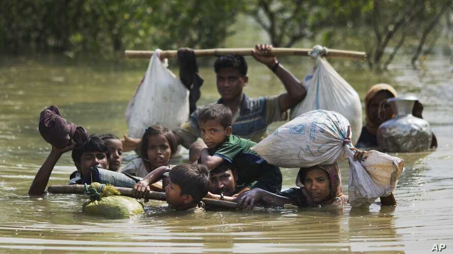 A Rohingya family reaches the Bangladesh border after crossing a creek of the Naf river on the border with Myanmmar, in Cox's Bazar's Teknaf area, Sept. 5, 2017.