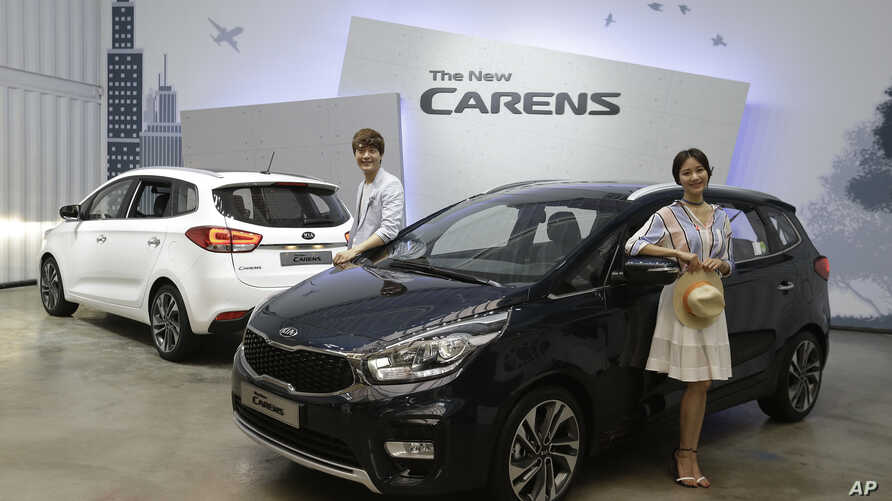 Models pose next to Kia Motors Corp.'s New Carens during its unveiling in Seoul, South Korea, Tuesday, July 26, 2016.