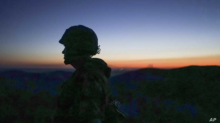A Russia-backed rebel guards the position after sunset near Donetsk, eastern Ukraine, Aug.  2, 2015.