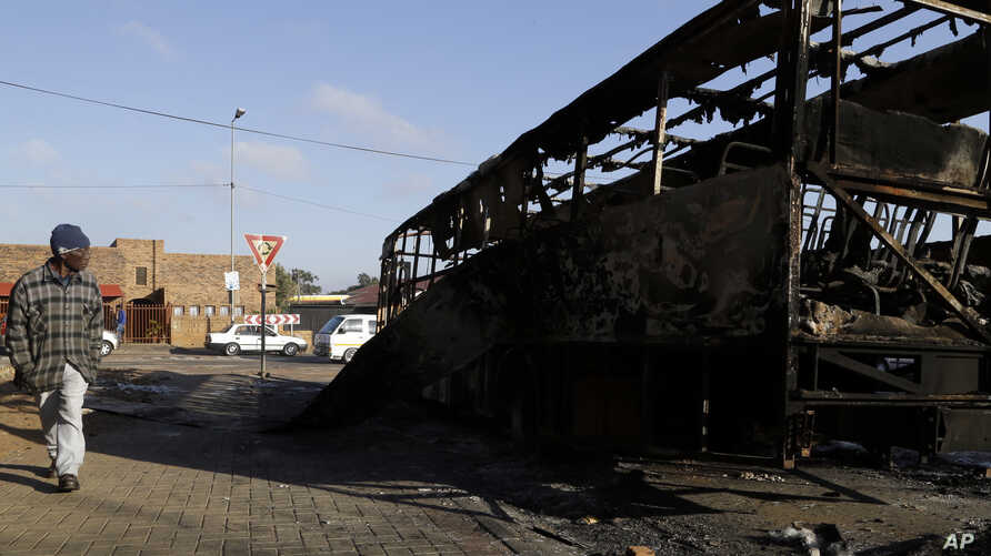 A man walks past a burnt-out bus after riots, in Atteridgeville, Pretoria, South Africa, June 22, 2016.