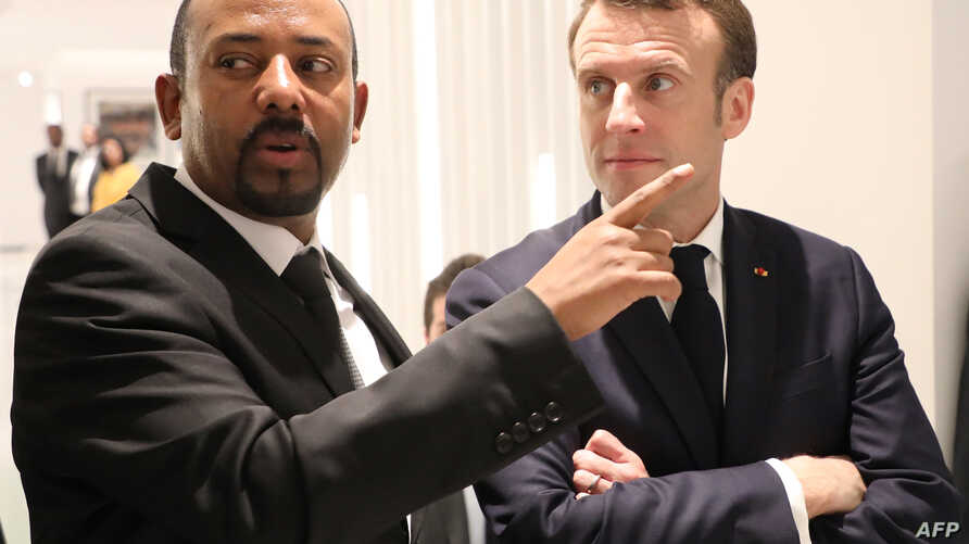Ethiopian Prime Minister Abiy Ahmed (L) speaks with French President Emmanuel Macron (R) before a meeting in Addis Ababa, March 12, 2019.