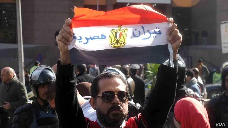 "Man holds Egyptian flag with Arabic words ""Tiran is Egyptian"" in front of the Egyptian Administrative Court in Giza, Egypt, Jan 16, 2017. (Photo: Hamada Elrasam for VOA)"