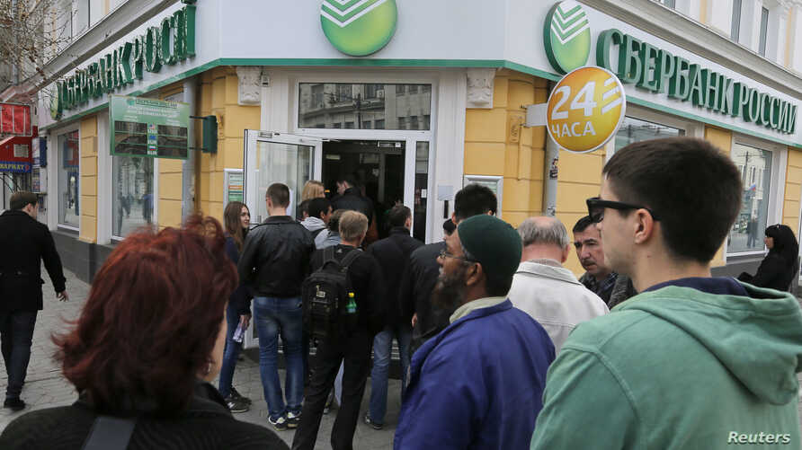 People stand in a line as they wait to enter a branch of Sberbank of Russia bank in the Crimean city of Simferopol April 7, 2014.