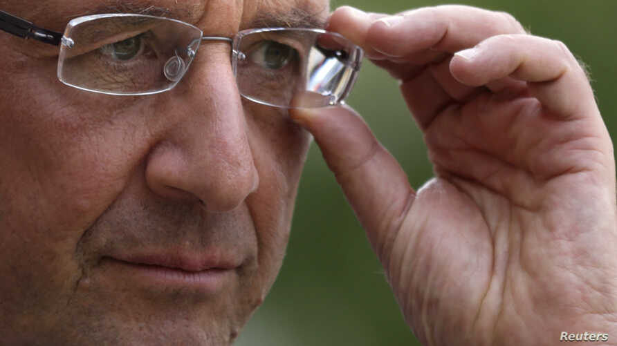France's President Francois Hollande adjusts his glasses after a meeting at the Elysee Palace in Paris, September 20, 2012.