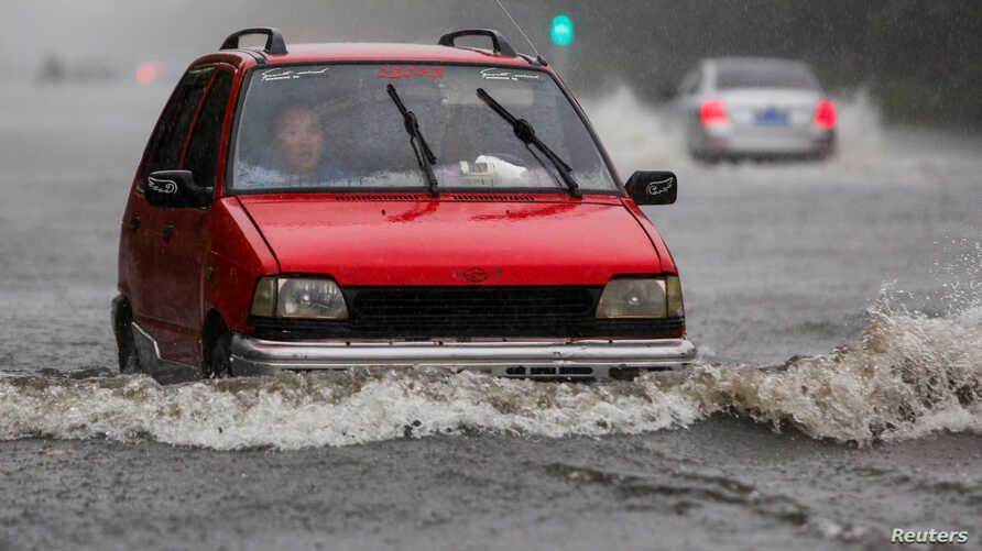 A car makes its way through a flooded street in the rain, in Lianyungang, Jiangsu province, China, June 23, 2016. Two weeks of torrential rains have been plaguing entire regions in eastern and southern China.