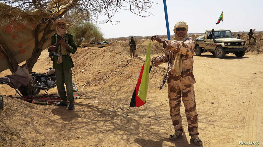 A fighter with the Tuareg separatist group MNLA (National Movement for the Liberation of Azawad) brandishes a separatist flag for the region they call Azawad outside the local regional assembly, where MNLA members met with the Malian army, the U.N. m