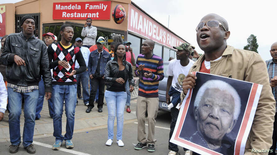 People sing and dance during a gathering of mourners on Vilakazi Street in Soweto, Dec. 6, 2013.