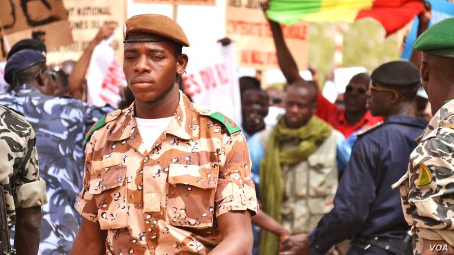 A national guard soldier walks by demonstrators at Bamako airport, Mali, March 29, 2012.  (VOA - N. Palus)