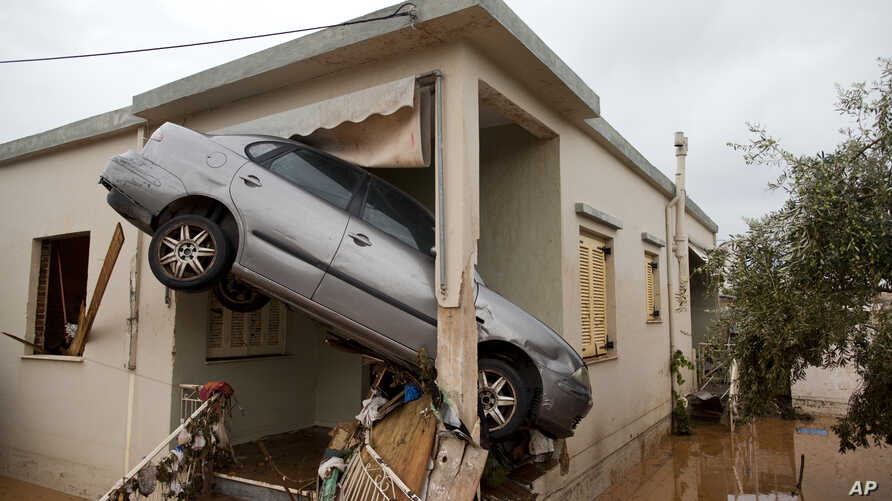 A car rests at the entrance of a flooded house after the water has receded in the town of Mandra, Greece, Nov. 16, 2017.