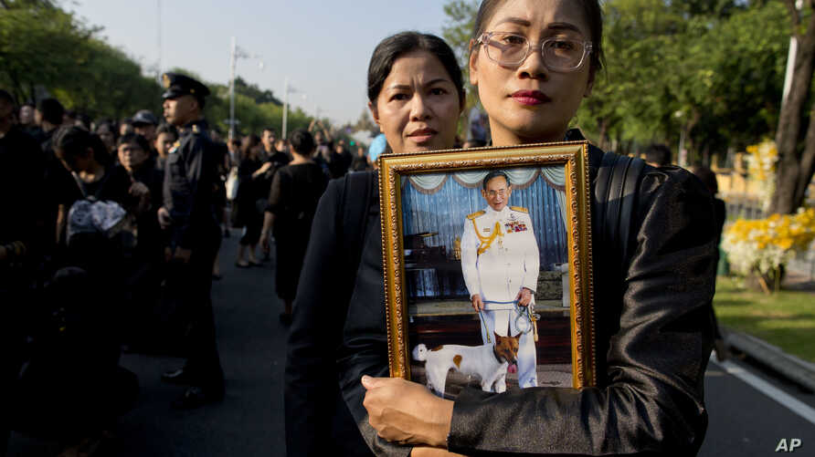 Thai mourners, carrying a portrait of late Thai King Bhumibol Adulyadej, gather in front of a replica of the royal crematorium in Bangkok, Thailand, Oct. 26, 2017.