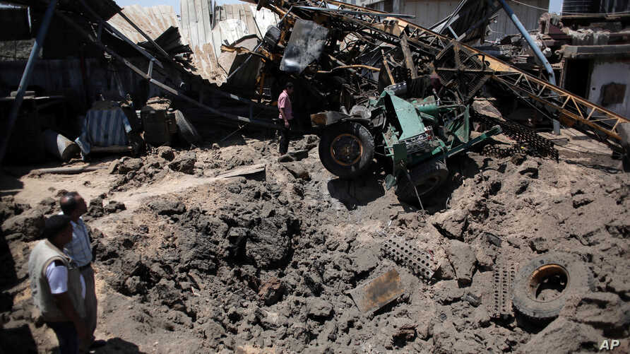 A Palestinian man inspects a damaged artesian well drilling truck after an early morning Israeli airstrike hit a workshop in Gaza City, Saturday, July 2, 2016.