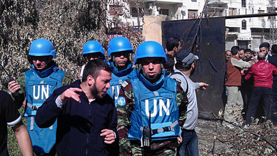 A handout picture released by the Syrian opposition's Shaam News Network shows Syrian residents talking to Moroccan UN observer, Colonel Ahmed Himmiche (R) during the monitors' visit to the Khalidiya district in the restive city of Homs, April 21, 20