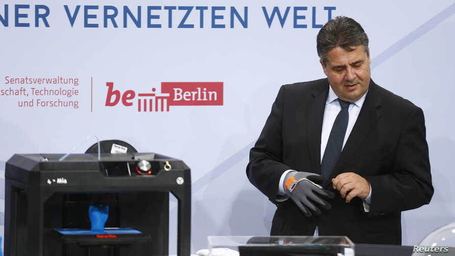 FILE - German Economy Minister Sigmar Gabriel is seen examining items at a technology summit in Berlin, Germany, Nov. 19, 2015.