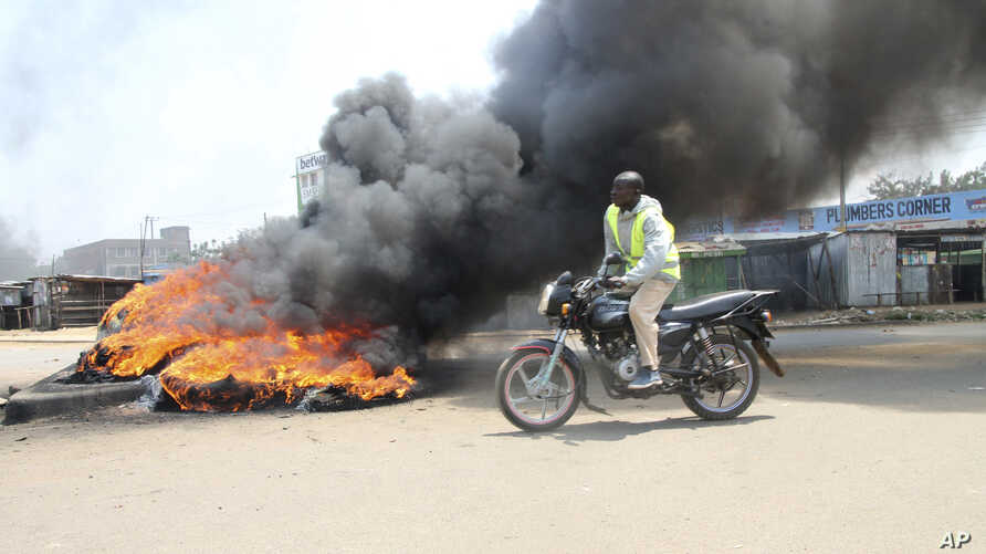 A motorcycle rider passes burning tires blocking a road in the Kondele area of Kisumu, Kenya, during protests in support of Kenyan opposition leader and presidential candidate Raila Odinga, Aug. 9, 2017.