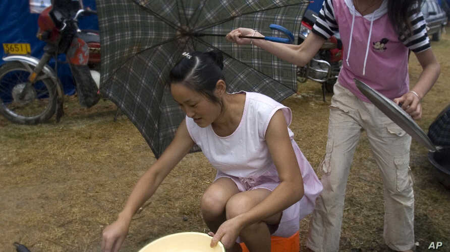 FILE - A child holds an umbrella as a Chinese woman tries to cook in the rain.