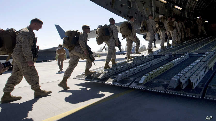 FILE - U.S. Marines board a military transport plane.
