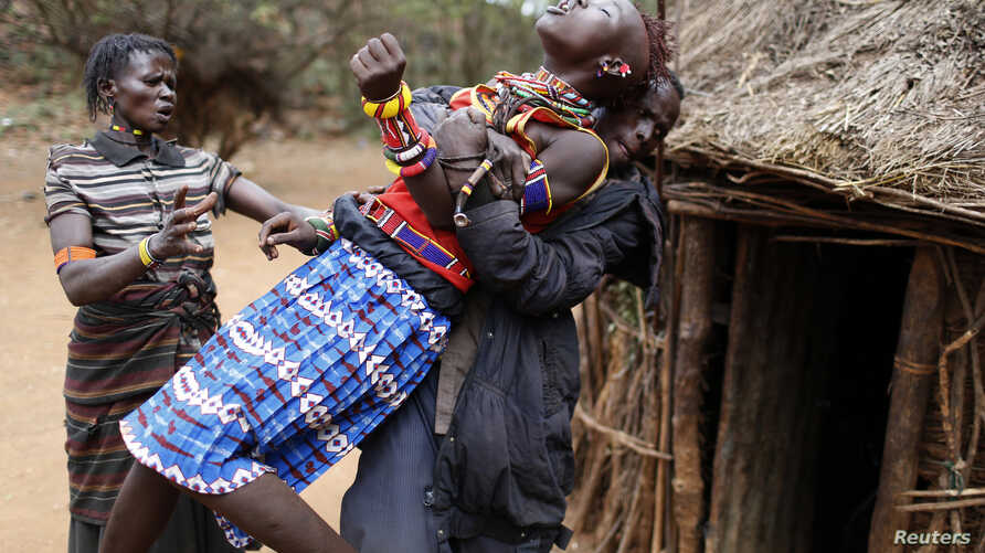 A man holds a girl as she tries to escape when she realised she is to to be married, about 80 km (50 miles) from the town of Marigat in Baringo County December 7, 2014. As Pokot tradition dictates, the future husband arrived to her family home with a