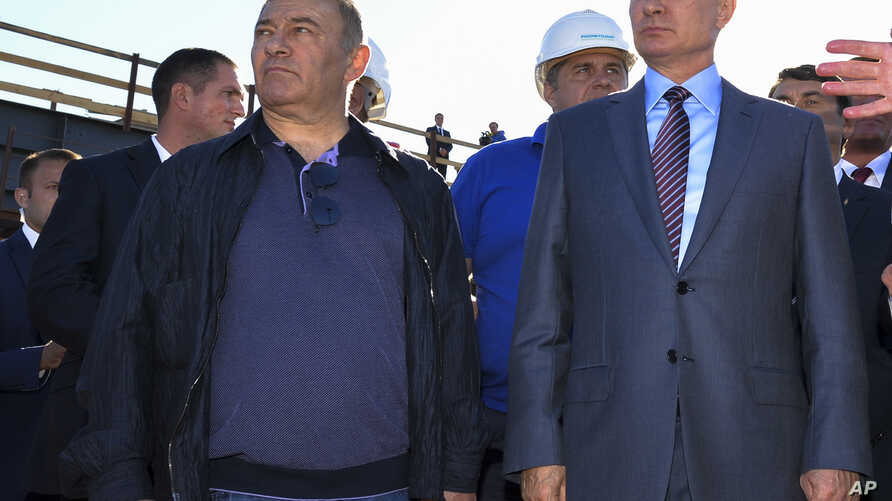FILE - Russian President Vladimir Putin, right, flanken by businessman and billionaire Arkady Rotenberg, visit the construction site of the Kerch Strait bridge in Kerch, Crimea, Sept. 15, 2016.
