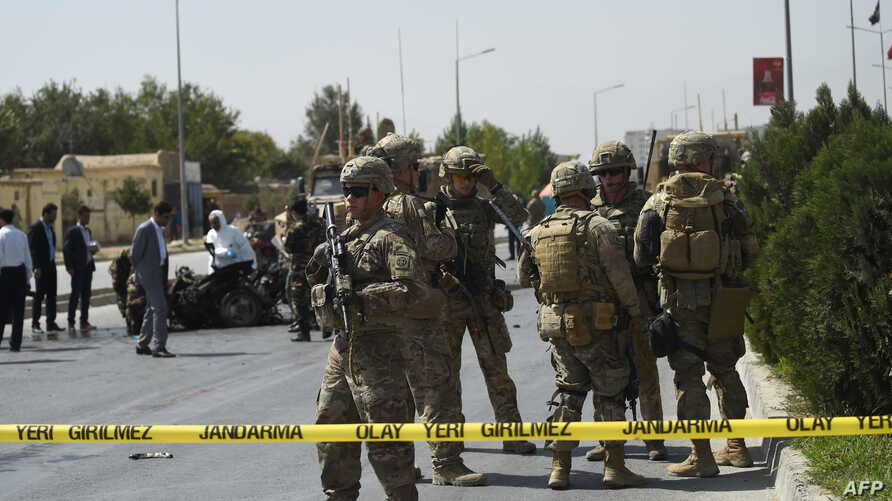 FILE - U.S. soldiers and Afghan security personnel investigate at the site of an attack in Kabul, Afghanistan, Sept. 24, 2017.
