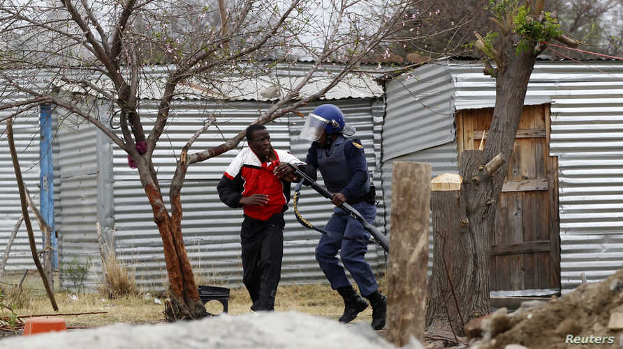 A man is arrested by police at Lonmin's Marikana mine in South Africa's North West Province, September 15, 2012.